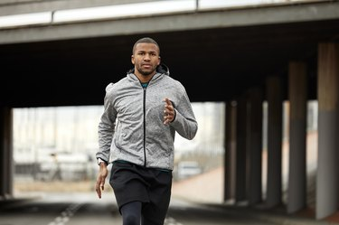 Portrait of young athlete jogging on road in city