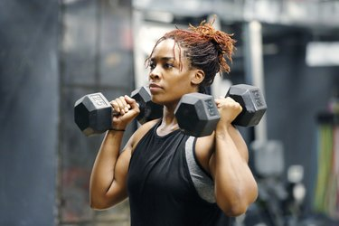 Fit young Black woman working out with dumbbells