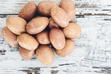 Тew potatoes on vintage wooden table top view