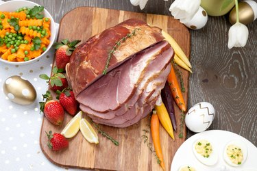Ham on cutting board with carrots and strawberries