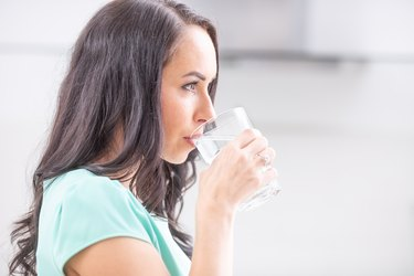young woman drinks clean water adheres to drinking regimen
