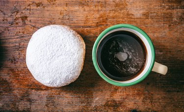 Coffee and krapfen with powder sugar, two, top view and isolated, wooden background.