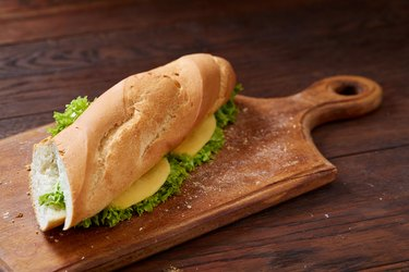Fresh and tasty sandwich with cheese and vegetables on cutting board over wooden background, selective focus.