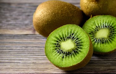 Halved potassium-rich kiwi on wood table in front of other whole kiwis