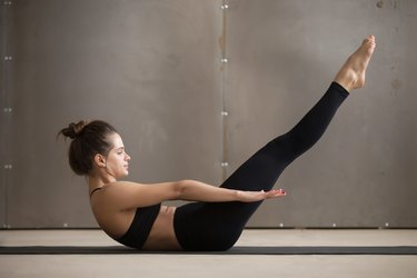 Young attractive sporty woman doing boat pose, grey studio backg