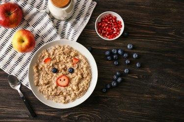 Plate with creative porridge for children on dark wooden table