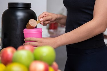 Healthy women preparing a whey protein after doing weight training in the kitchen with fresh fruits as a blurred foreground.