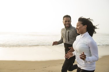 Man and woman running on the sand