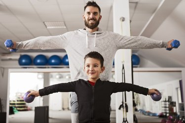 Father and son performing lateral raises.
