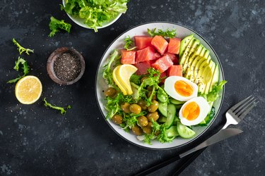Ketogenic, paleo diet lunch bowl with salted salmon fish, lemon, avocado, olives, boiled egg, cucumber, green lettuce salad and chia seeds, healthy food trend, top view