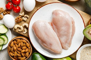 top view of fresh raw chicken breasts near nuts, eggs and vegetables, ketogenic diet menu