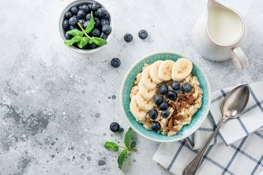 Oat porridge with banana, chocolate and fresh blueberry in a bowl on a light gray slate, stone or concrete background. Top view.