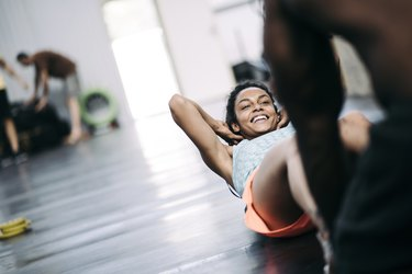 Young black girl doing crunches with her friend