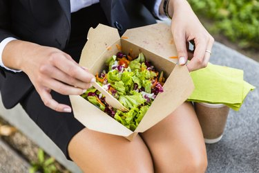 Businesswoman having lunch outdoors, partial view