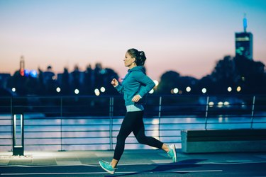 A woman jogging in the city at night before bed