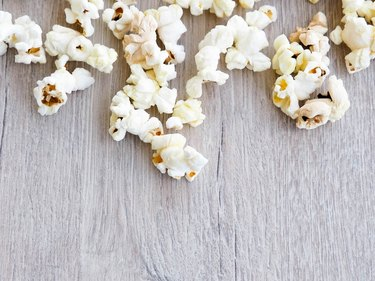 popcorn on wooden background, copy space, Scattered salted popcorn, texture background.