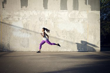 Woman jogging on street by wall
