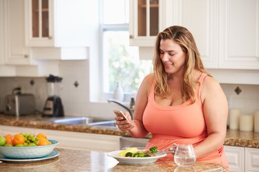 Woman Eating Healthy Meal And Using Mobile Phone