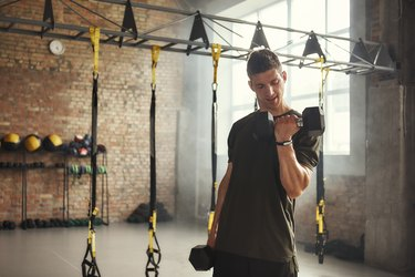 man doing biceps curls with dumbbells during upper-body workout while standing against of brick wall at gym