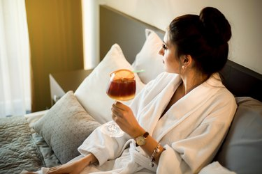 A young woman in a bathrobe enjoys bed and drinks a cocktail