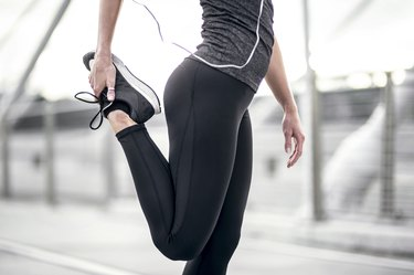 Athletic female figure stretching wearing running pants