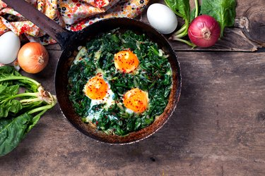 Braised spinach and eggs in an old frying pan with immune boosting foods