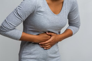 Woman suffering from gastritis, touching her tummy
