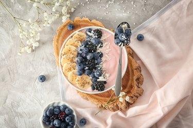 Bowl with pink yogurt and fresh fruits on light table