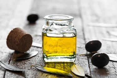 Olive oil in a glass bottle and fresh olives