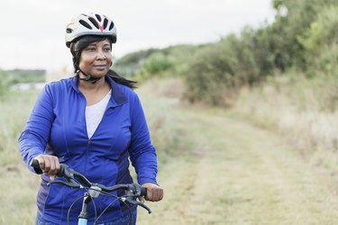 Black woman riding bike in park with helmet