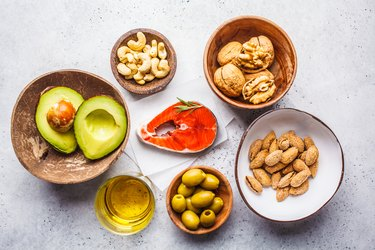 Top view of a variety of foods with healthy fats, including fish, nuts, oil, olives and avocado