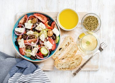 Greek salad with olive oil, bread, spices and white wine