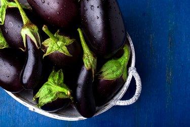 Fresh eggplant in grey basket on blue wooden table.Rustic background. Top view. Copy space. Vegan vegetable.