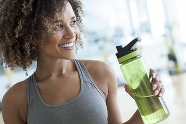 A woman drinking water because she's doing intermittent fasting to boost her mood