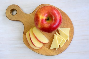 Weight Watchers snack of an apple with cheddar cheese slices on a wooden cutting board