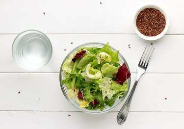 Mixed salad in glass bowl with flax seed and water on white wooden table.