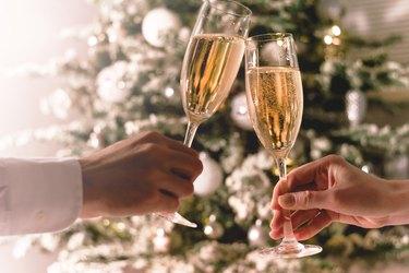 Couple holding glasses of sparkling wine for keto christmas dinner