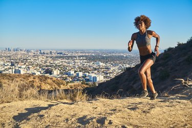 fit african american woman running at runyon canyon with los angeles