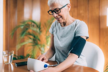 An older woman using a blood pressure app to monitor her blood pressure at home