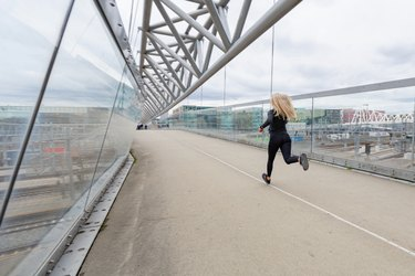 Woman runner during fast running exercise in modern city at cloudy day
