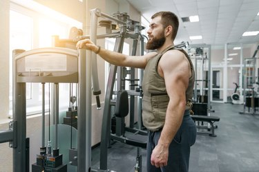 Man resting during HIIT workout with weight vest.