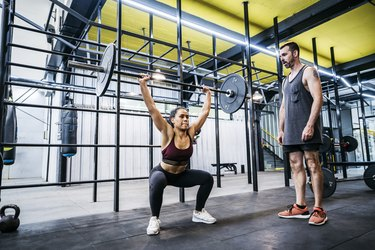 Female athlete squatting and deadlifting with trainer