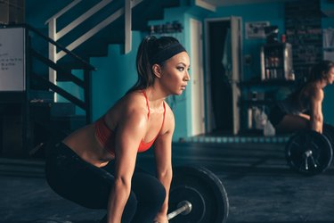 Woman crouching to lift barbell in gym