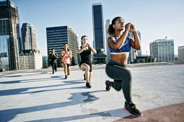 Woman stretching legs on urban rooftop