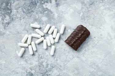 High Protein bar and Arginine capsules.  Bodybuilding food supplements on bright stone background. Directly Above. Copy space.