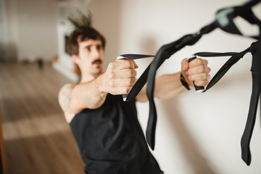 adult man practicing suspension training at modern home