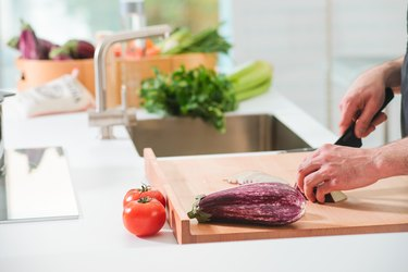 Cropped Hands Of Man Cutting Eggplant On Kitchen Island