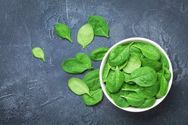 Green spinach leaves in bowl on black table top view. Organic and diet food.