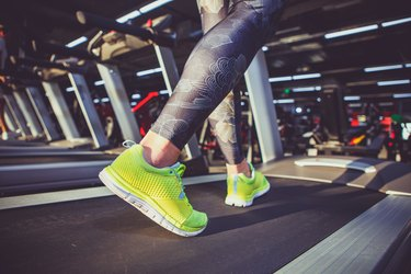 Theme of sport and weight loss. Close-up of the foot of a young strong woman in a light green sneakers on a simulator, running in the gym. Preheating before training, cardio training