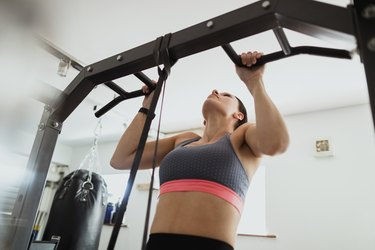 Woman using an at-home pull-up bar doing a workout in her spare room